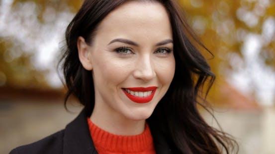 Woman with Vivid Makeup Smiling Playfully
