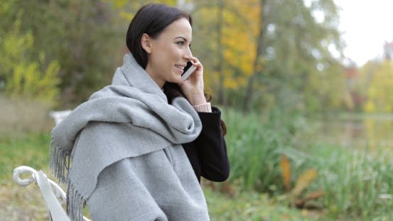 Thumbnail for Pretty Woman Speaking on Phone in Park