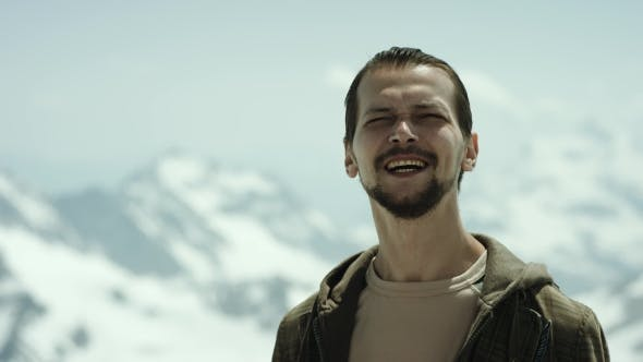 Young Bearded Man at Mountain Pinnacle with Scenic View Squint Eyes and Talking