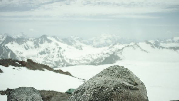 Thumbnail for Hiker Feet in Leather Boot Stomps on Rock at Snowy Mountain Scenic View