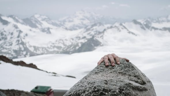 Young Guy Climber Ascents Rock at Snowy Mountain Scenic View on Sunny Day