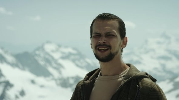 Thumbnail for Young Bearded Man at Mountain Summit with Scenic View Squint Eyes and Talking