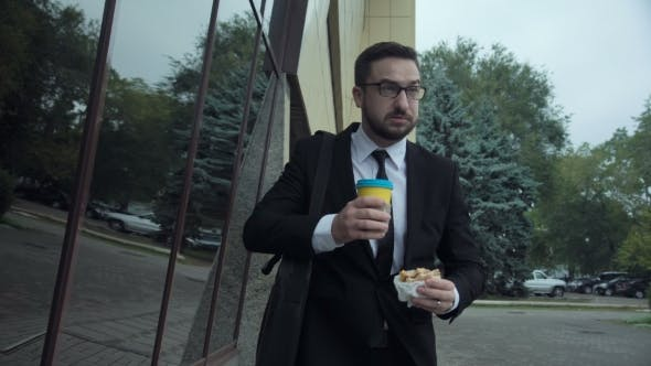 Thumbnail for Businessman Eating Burger and Drinking Coffee