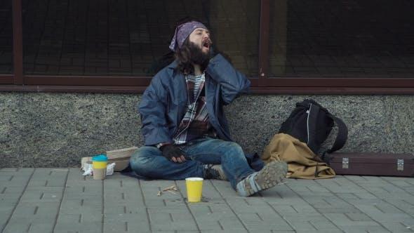 Thumbnail for A Drunken Homeless Man Is Sitting on the Street.