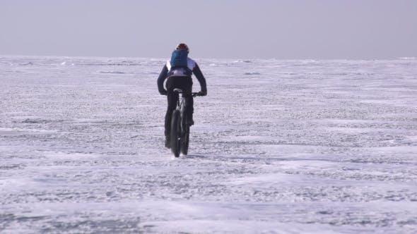 Thumbnail for a Sportive Man Riding a Bicycle Across a Frozen Lake