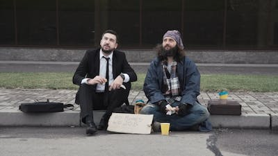 Businessman and Homeless on Pavement
