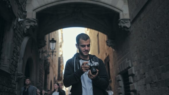 Thumbnail for Young Man Walks with Camera in Old Town
