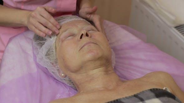 Professional Beautician Massaging Human Face