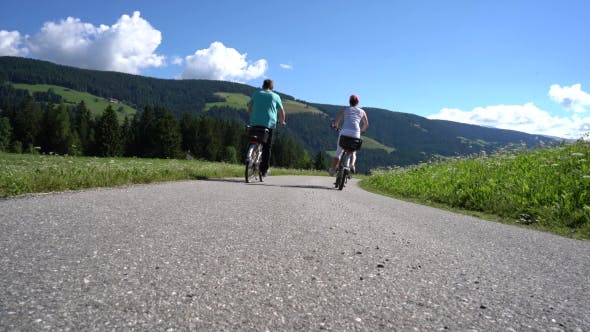 Thumbnail for Couple Woman and Man on Electric Eco Bike Cycling Italy Dolomites Alps