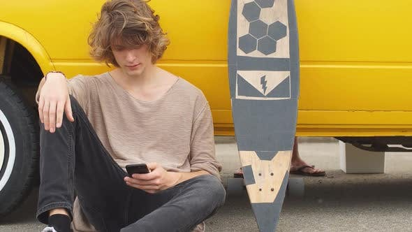 Thumbnail for Young Hipster Guy Sitting Next His Yellow Car During Road Trip.