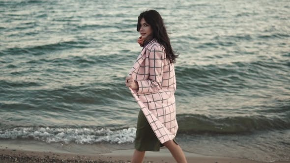 Thumbnail for Cute Girl in Autumn Coat Walks Along the Beach at Sunset. Girl Posing for the Camera Outdoors