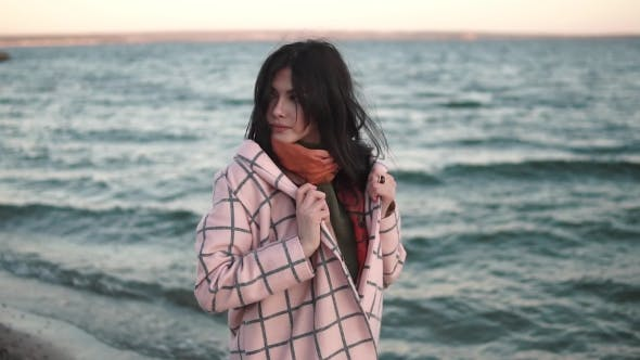 Thumbnail for Portrait of a Beautiful Young Woman on the Beach. Girl in Autumn Coat Outdoors