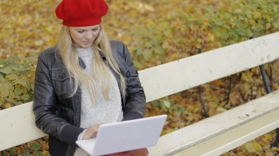 Thumbnail for Pretty Woman Using Laptop in Autumn Park