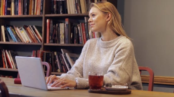 Thumbnail for Woman in Jumper Using Laptop in Library