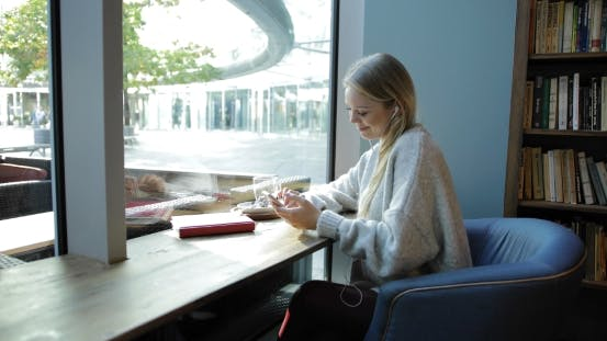 Thumbnail for Woman Using Smartphone in Front Window