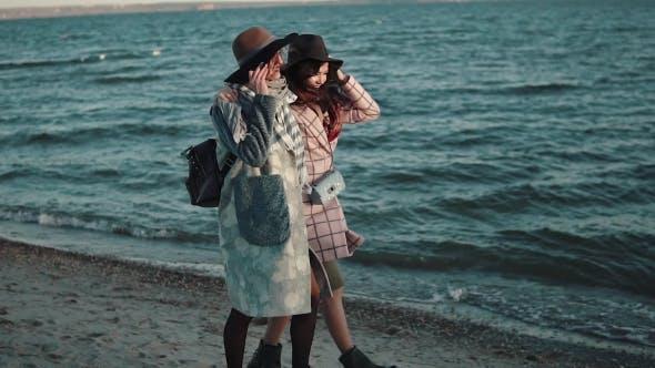 Thumbnail for Unbeschwerte Freundin Gehen Sie am Strand bei Sonnenuntergang entlang und genießen Sie den warmen Herbstabend. Zwei Mädchen in