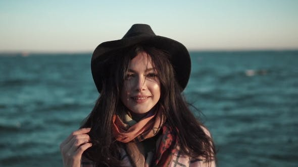 Thumbnail for Portrait of a Young Woman on the Beach. Girl in Hat and Autumn Coat Smiling and Posing on Camera By