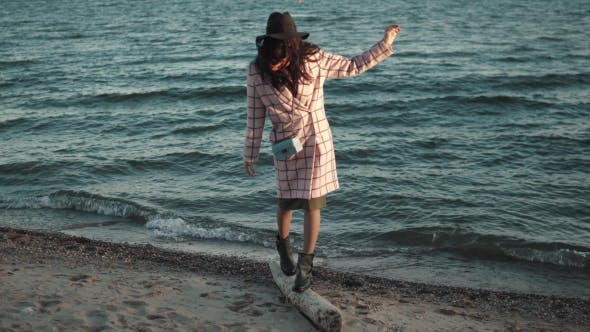 Thumbnail for Cute Girl in Autumn Coat Walks Along the Beach at Sunset. Young Woman Enjoying Warm Autumn Day