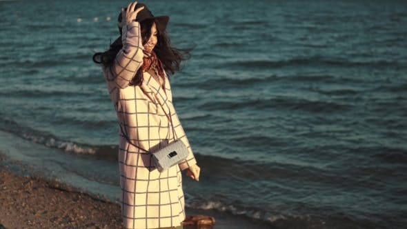 Thumbnail for Young Woman Enjoying a Warm Autumn Afternoon By the Water. Girl in Autumn Coat and Hat Walking Along