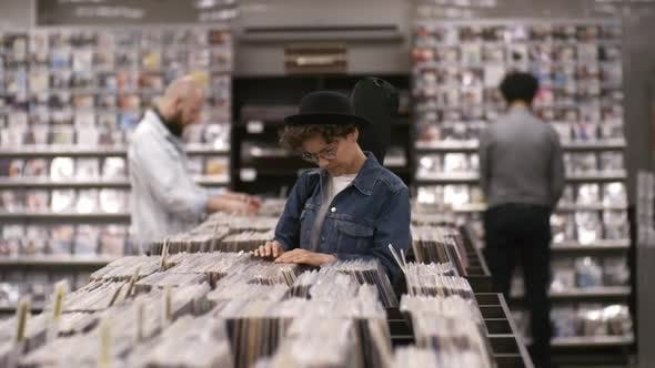 Thumbnail for Caucasian Woman with Guitar Case Browsing through Vinyl in Record Shop