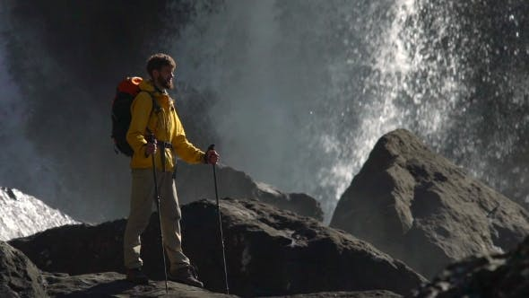 Thumbnail for A Male Hiker Watches a Big Waterfall in .