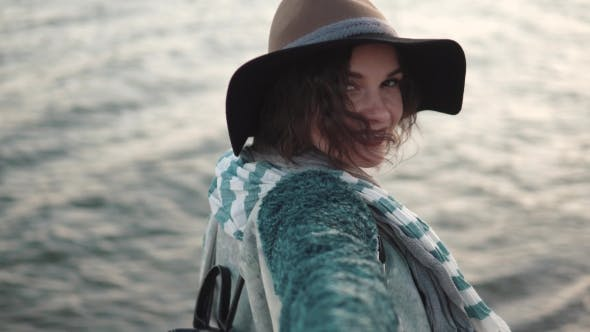Thumbnail for Follow Me. Beautiful Young Woman Walks Along the Coast, Smiling and Enjoying the Warm Autumn Day