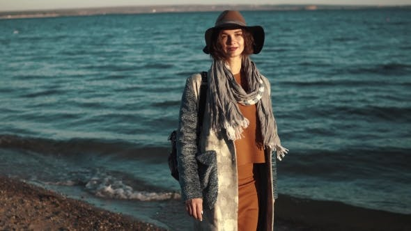Thumbnail for Portrait of Cute Girl in Autumn Coat Against the Sea. Girl Posing at Camera and Smiling