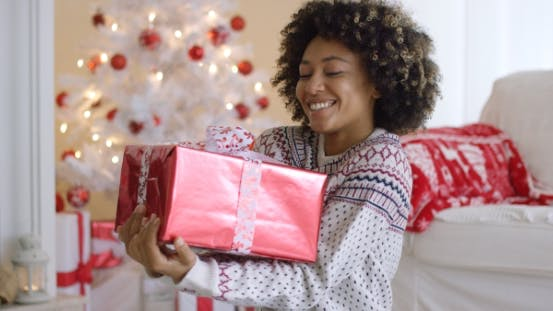 Thumbnail for Happy Young Woman Holding a Christmas Gift