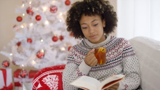 Thumbnail for Woman Reading a Book in Front of a Christmas Tree