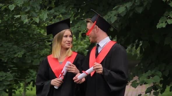 Thumbnail for Smiling Couple of Graduates Walking in Park, Holding Diplomas and Talking