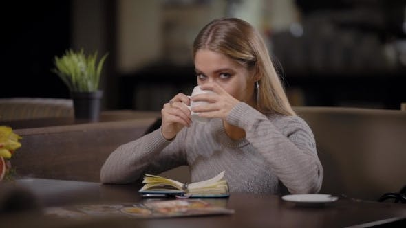 Thumbnail for A Young and Pretty Woman Enjoys the Taste of Coffee in a Restaurant