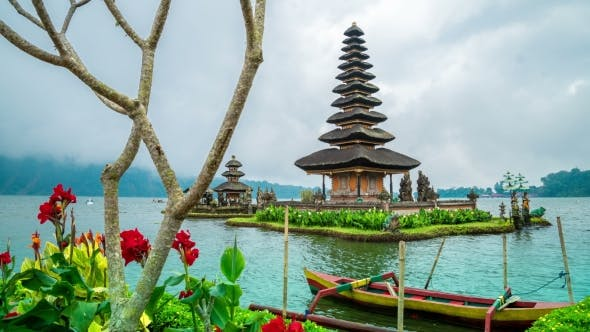 Cover Image for View of Red Flowers and Temple Pura Ulun Danu Batur in Bali, Indonesia.