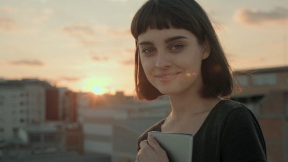 Thumbnail for Attractive Brunette with Gadget on Rooftop at Sunset