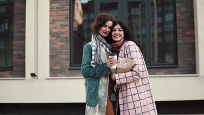 Portrait of Two Girlfriends Against a Background of Modern Architecture. Girlfriends Embrace
