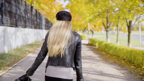 Thumbnail for A Young Woman Who Is Stylishly Dressed, Strolls Along the Autumn Street with a Bag in Her Hand