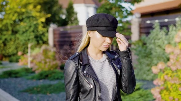 Thumbnail for A Modern Woman in a Cap and Leather Jacket Is Walking Along the Street
