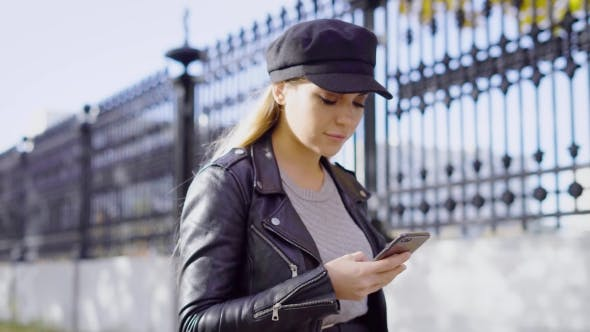Thumbnail for A Young and Attractive Woman Walks Down the Street and Prints a Message on the Smartphone