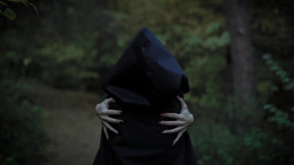 Thumbnail for a Woman in a Cloak with a Hood Embraces Herself Behind Her Hands with Long Nails, Like a Witch