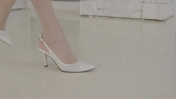 Thumbnail for Female Feet in White Shoes Walk Unhurriedly Along Lacquer Floor.