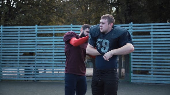 Thumbnail for Man Helping His Mate To Put on Football Jersey