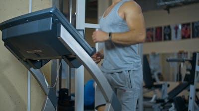 Bodybuilder Running on the Running Track in the Gym