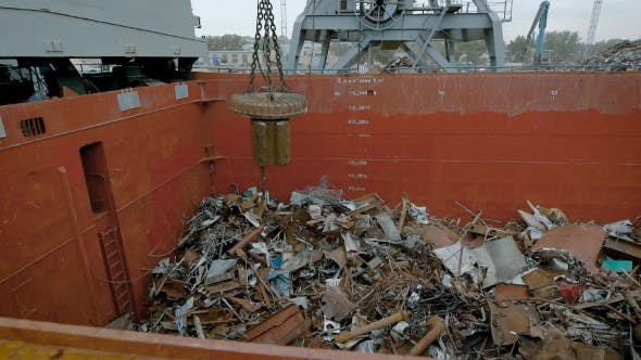 In a Large Container with Metal Debris Fall Iron Parts, a Mechanical Building Magnet Sends the Trash
