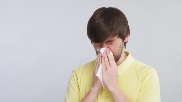 Thumbnail for Man with Cold Blows His Nose Into Tissue Wearing Yellow Shirt Isolated on Grey