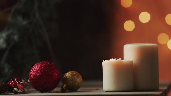 Thumbnail for . Christmas Candles Blow Out on the Background of Blurred Lights of a Christmas Tree The Smoke From
