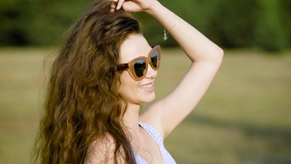 Thumbnail for Young Woman Wearing Sunglasses and Posing Happily on Nature Looking Away in Sunlight