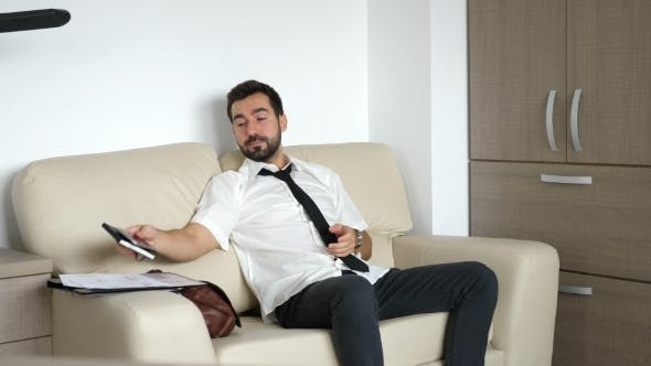 Thumbnail for Businessman on the Couch Streatching After Putting His Notebook and Phone Aside