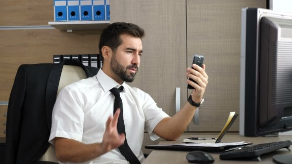 Thumbnail for Young Attractive Businessman Having a Video Conference Via His Phone