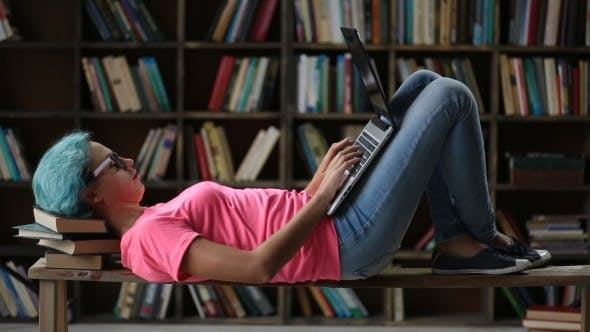 Thumbnail for Cute Girl with Laptop Lying on Bench in Library