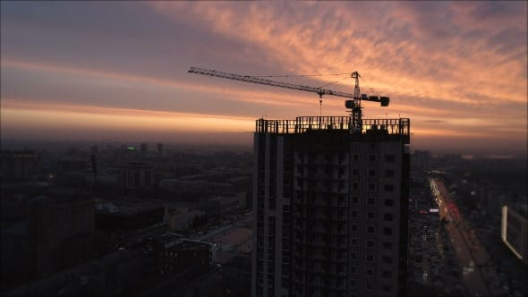 Cover Image for Yellow Tower Building Crane Fly Around Construction Site Building Apartments