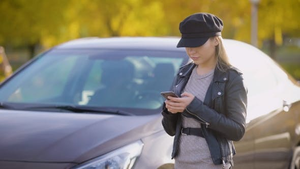 Thumbnail for Young Blonde Is Standing in a Parking Area Near Her Auto in Autumn Day, Checking E-mail, and Writing